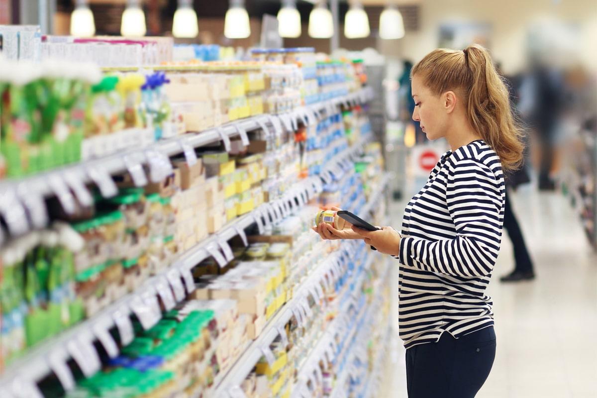 Femme lisant une étiquette alimentaire au supermarché