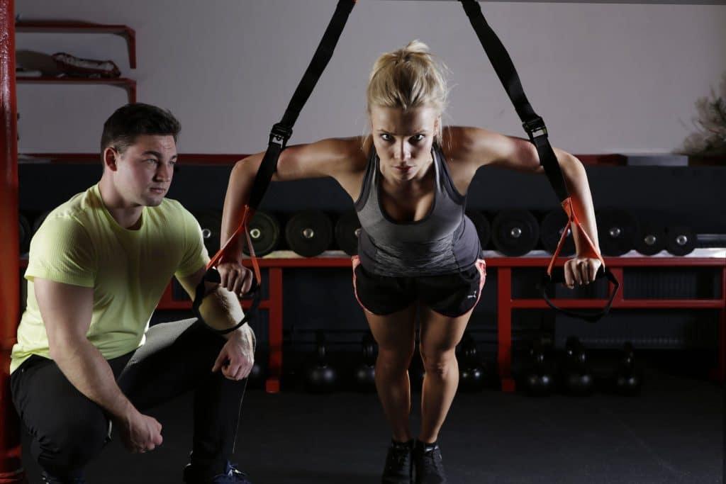 Femme qui s'entraîne avec des sangles accompagné d'un coach sportif