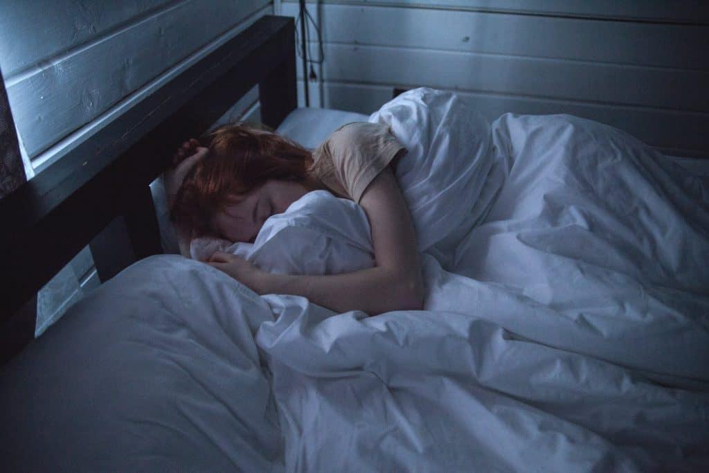 Femme qui se repose dans son lit sous les draps