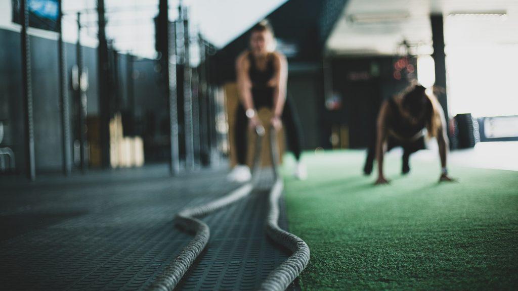 Femme faisant un exercice avec deux cordes dans une salle de sport